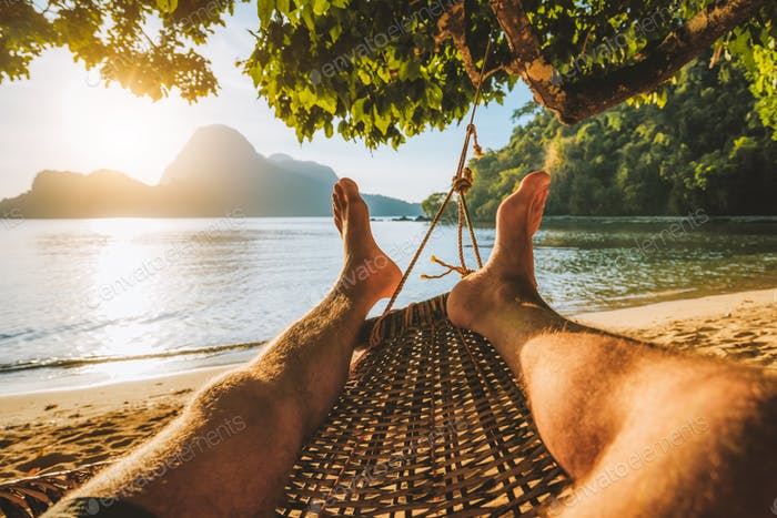Feet of adult man relaxing in a hammock on the beach during summer holiday