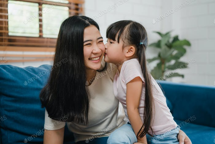 Asian family mom and daughter embracing kissing on cheek congratulating with birthday.