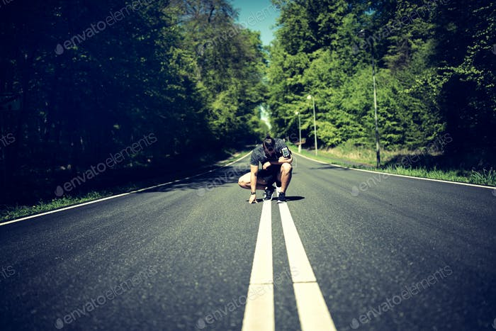 Man kneeling on a country road looking exhausted after jogging