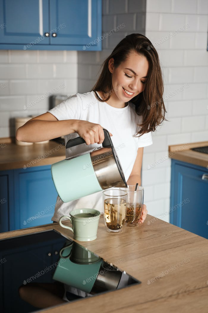 Image of cheerful beautiful woman smiling and making tea