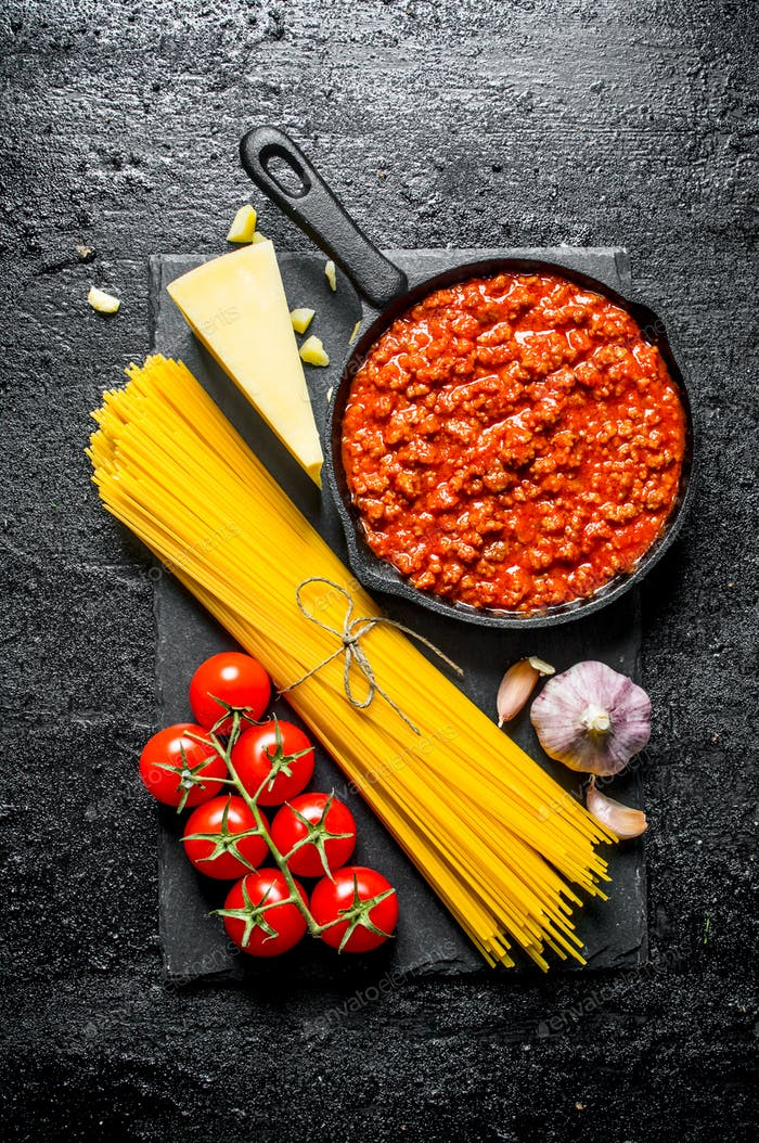 Pasta background. Dry spaghetti with Bolognese sauce, tomatoes and garlic.