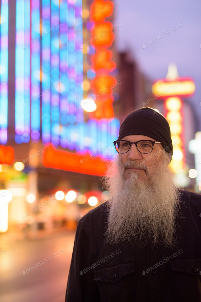 Mature bearded tourist man with eyeglasses thinking in Chinatown at night