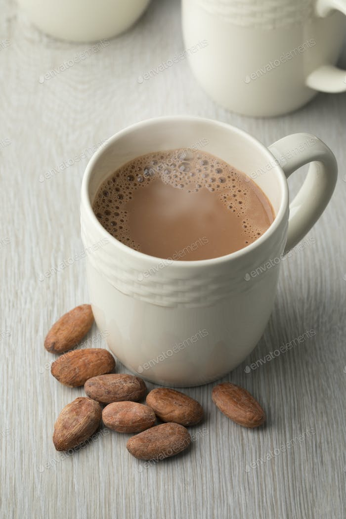 Mug with hot chocolate milk and cocoa beans