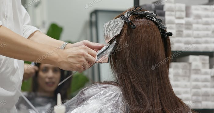 Stylist hairdresser makes hair coloring