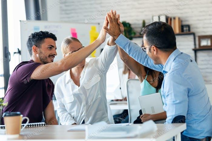 Erfolgreiches Geschäftsteam, das gute Arbeit feiert und gleichzeitig den Coworking-Platz in die richtigen Hände hält.