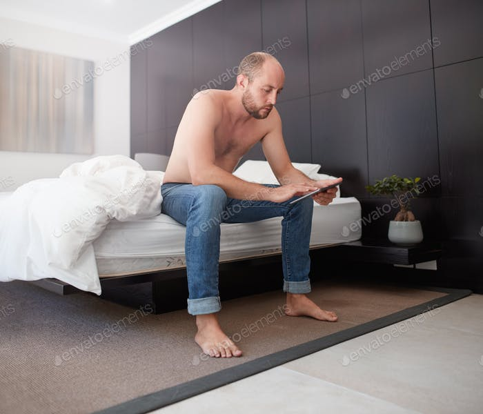 Handsome young man using a digital tablet in bedroom