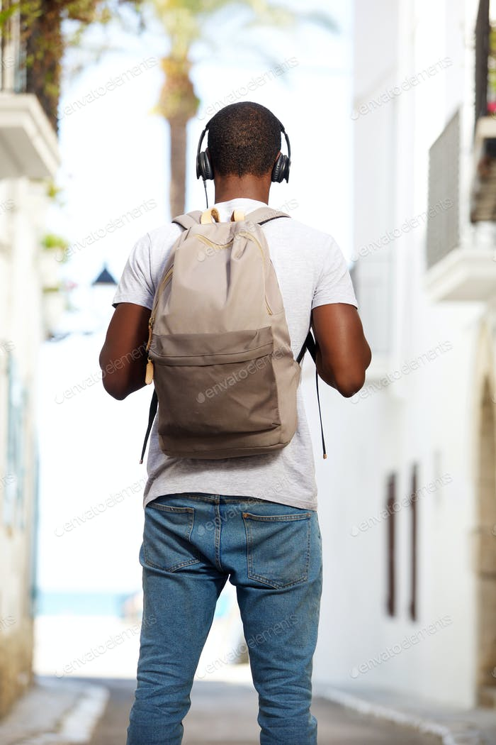 Young african american man with bag standing in street