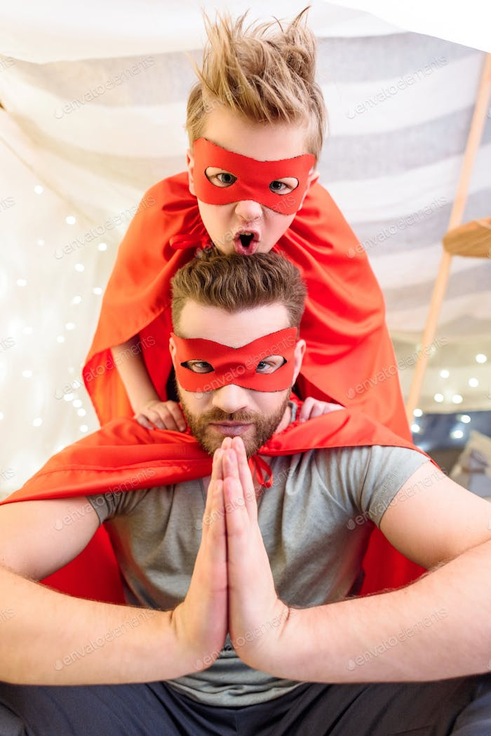 Father and son in superhero costumes playing together in blanket fort
