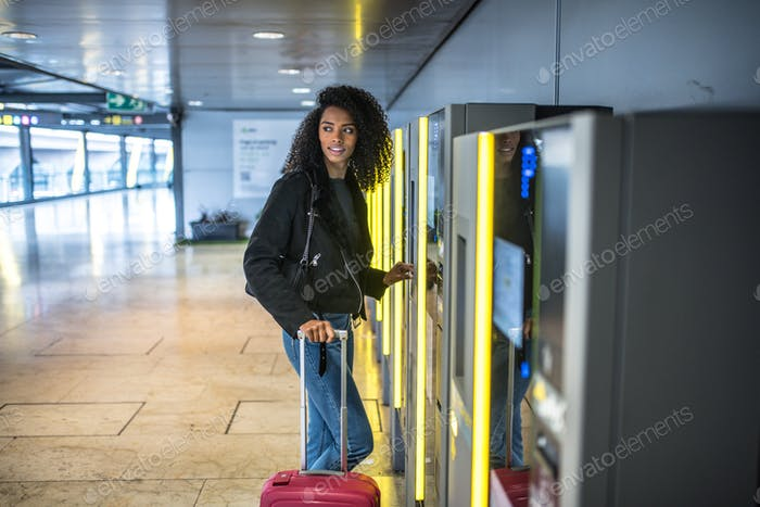 Mujer negra que paga en el aparcamiento de la máquina en el aeropuerto con una
