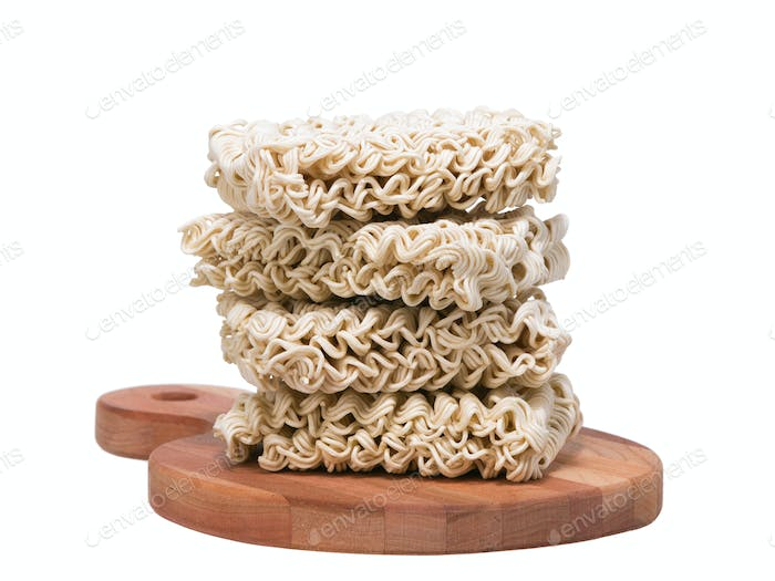Ramen instant raw noodles on wooden plank front general view