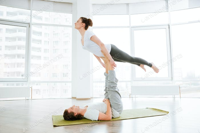 Beautiful young couple doing acro yoga in studio together