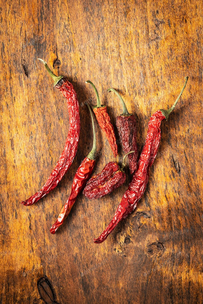 Dried red chili peppers on wooden table.