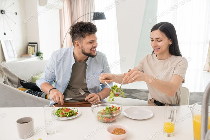 Young woman putting vegetable salad on plates