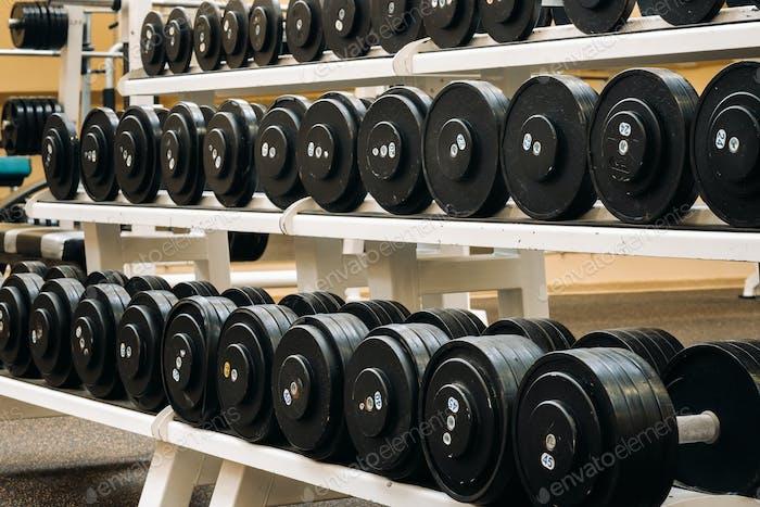 Reihen von Hanteln im Fitnessstudio mit hign Kontrast und monochromen Farbton