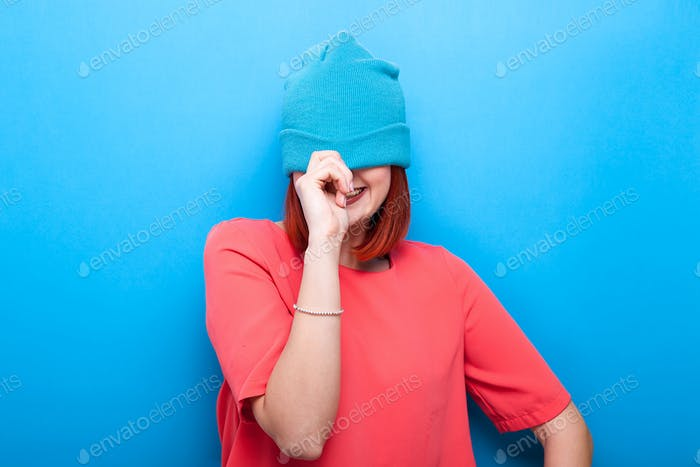 Happy smiling and laughing cool teenager girl wearing a blue hat