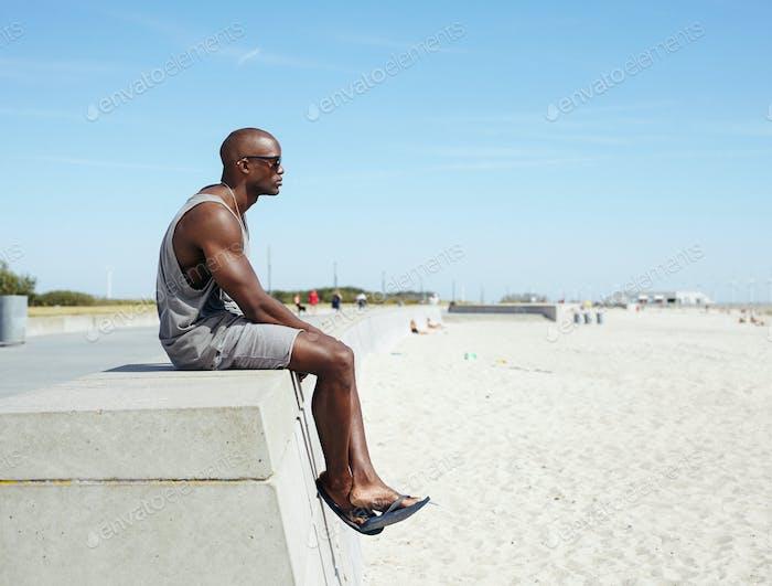 Afrikaner sitzt auf einer Strandpromenade