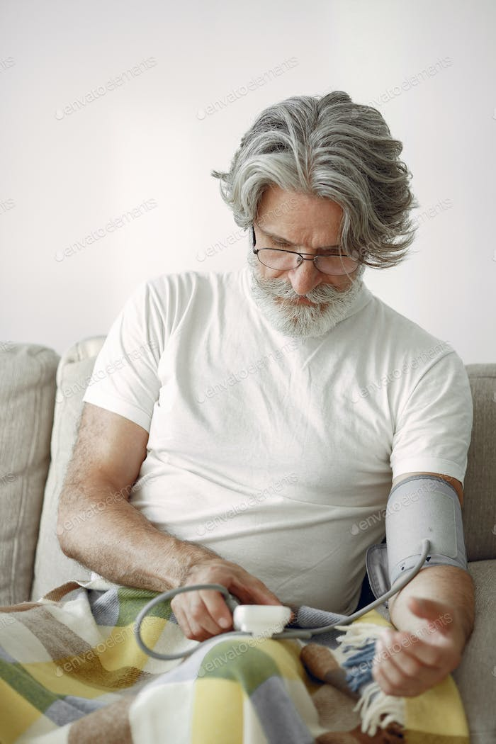 Mature man sitting and measuring his blood pressure