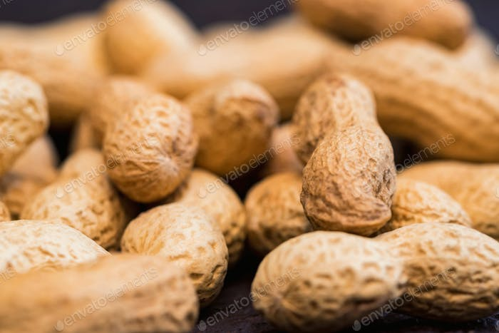 Close up pile of unpeeled peanuts on dark wooden background
