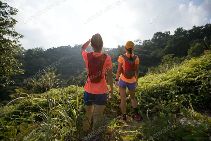 Two women trail runners rest and looking at the beautiful sunrise on mountain top