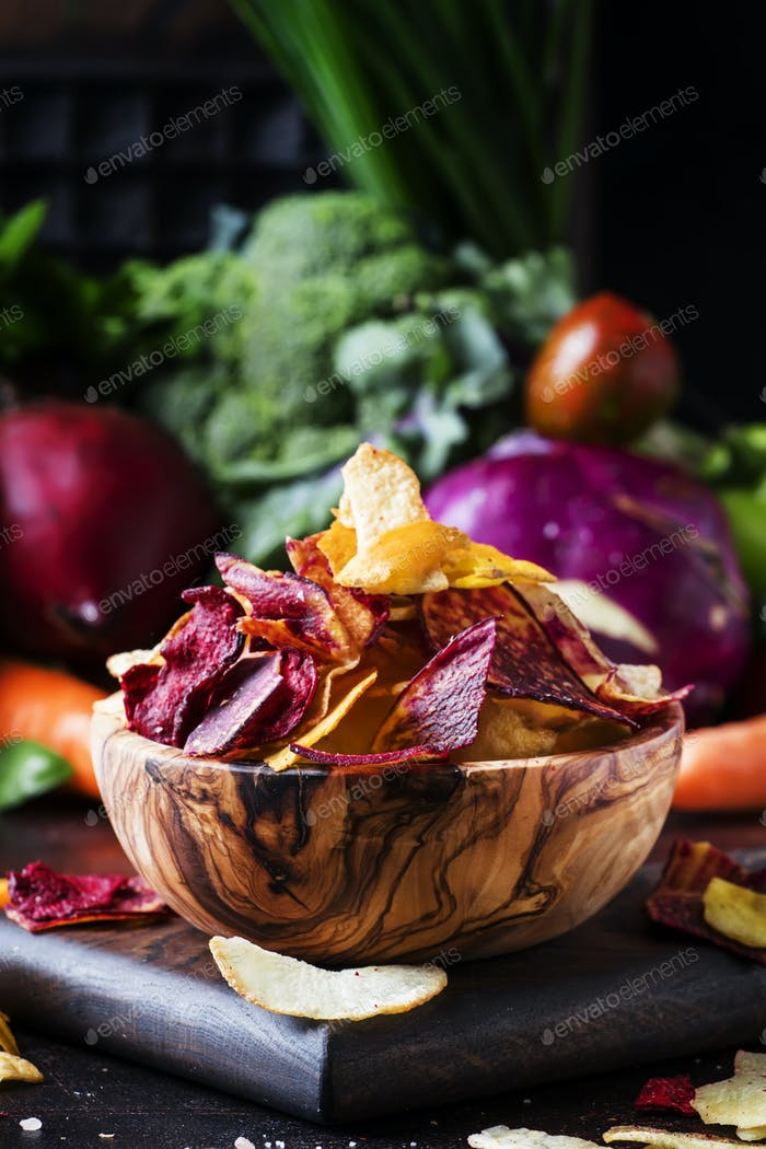 Vegan snacks, multicolored vegetable chips in wooden bowl