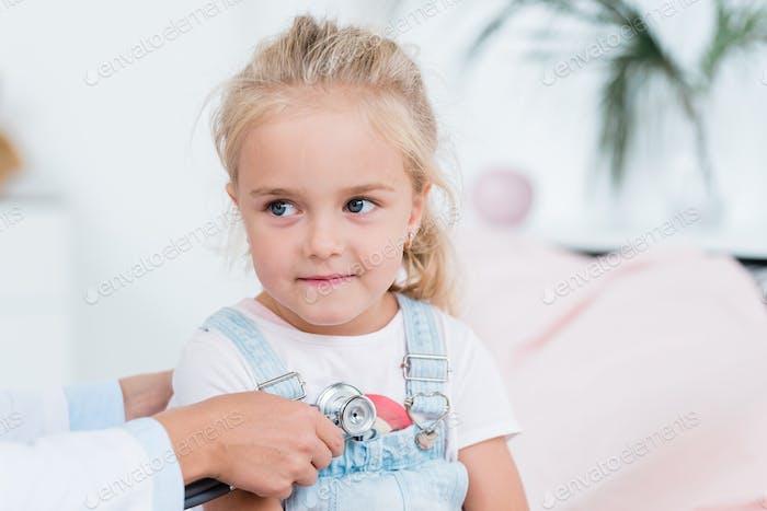 Linda niña con cabello rubio buscando en médico usando estetoscopio
