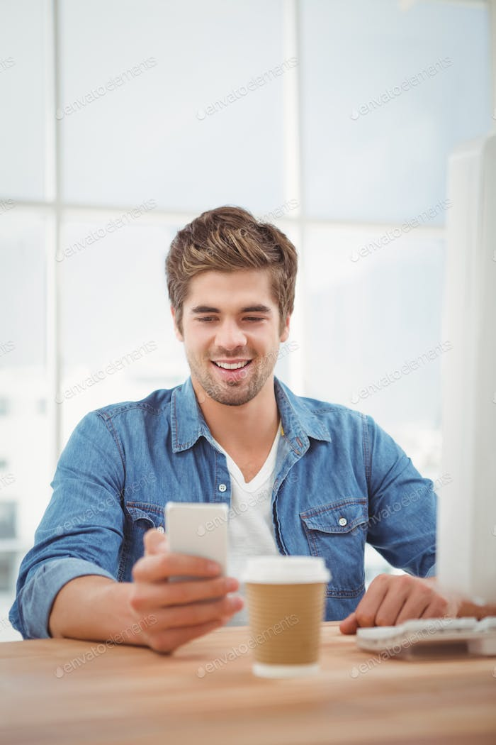 Happy hipster smiling while looking at mobile phone at desk in office