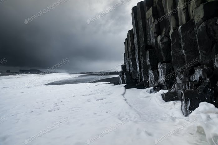 Basalt rock formations on black beach Reynisfjara at storm, Vik, Iceland