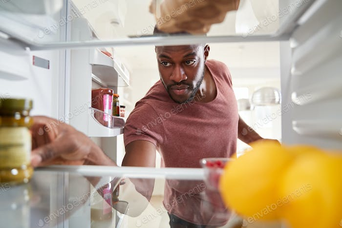 View Looking Out From Inside Of Refrigerator As Man Opens Door And Unpacks Shopping Bag Of Food