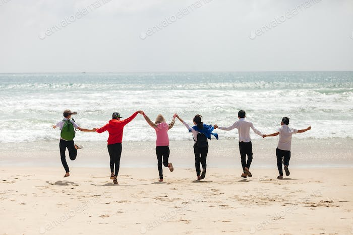 asian teenagers jumping on the beach together