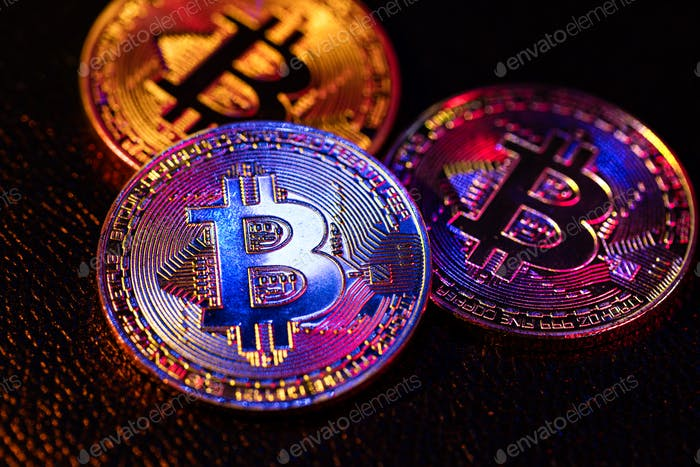 Three coins with bitcoin logo laying on a black background