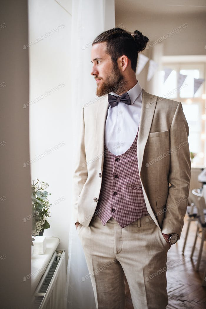 A handsome hipster young man with formal suit standing on an indoor party.
