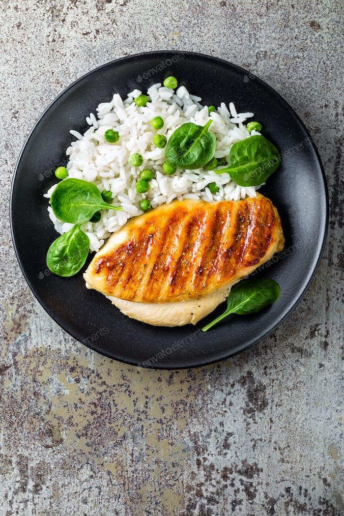 Hähnchenbrust oder Filet, Geflügelfleisch gegrillt und gekochter weißer Reis mit grünen Erbsen