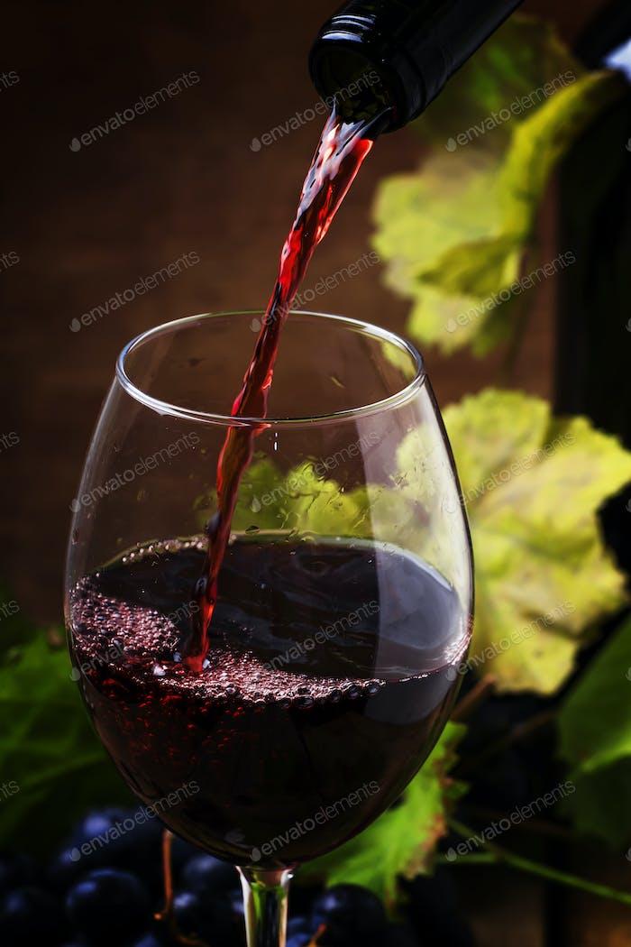 Rotwein gießt in ein Glas, Vintage-Holzhintergrund
