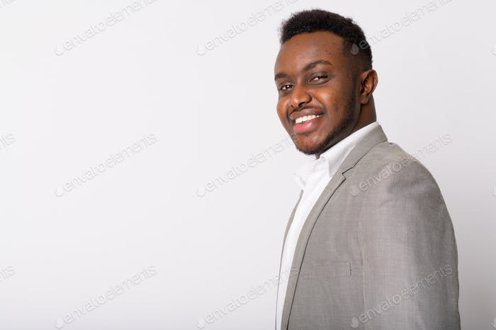 Profile view of happy young African businessman looking at camera