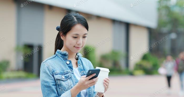 Frau Verwendung von Smartphone und halten Kaffeetasse