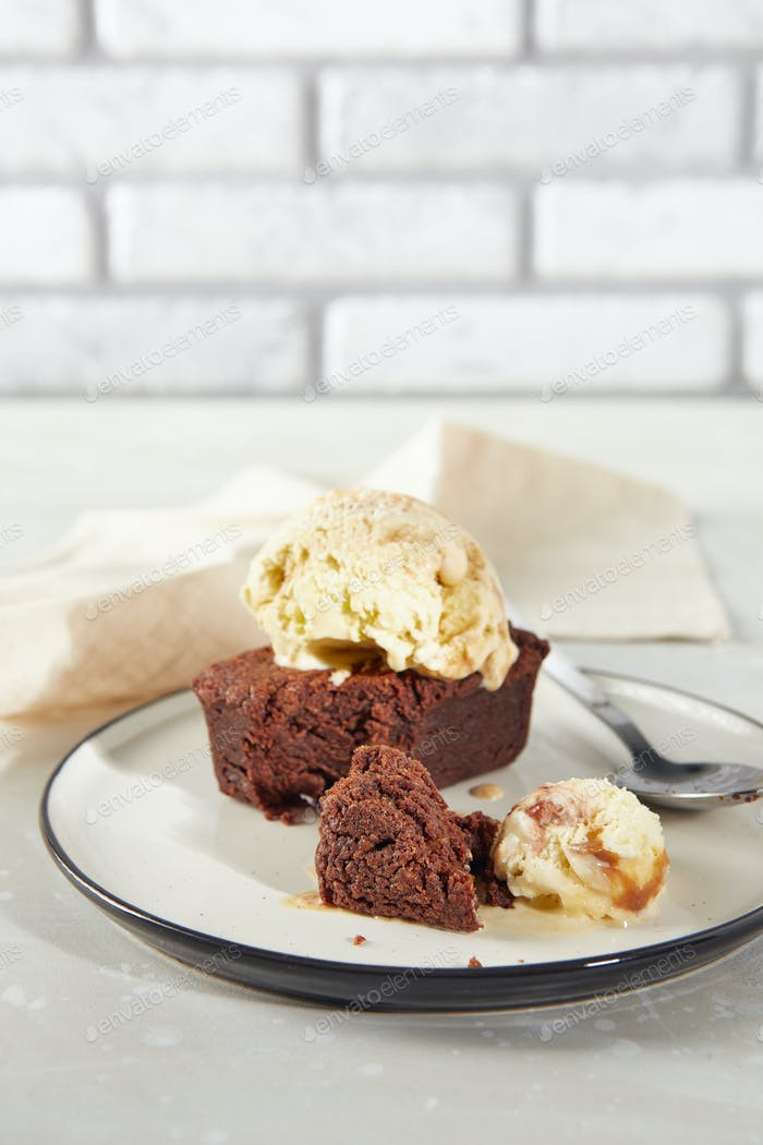 Brownie chocolate dessert with scoop of creamy nut ice cream on plate with napkin
