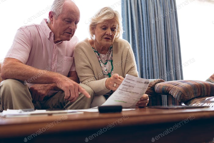 Couple discussing over medical bill while sitting on sofa at retirement home