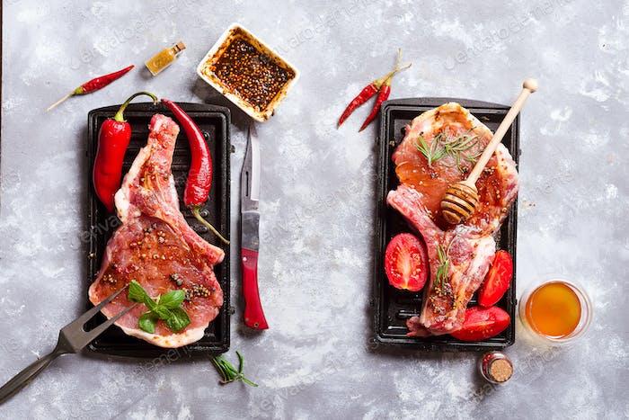 Rohe Steaks und Pfannen mit Gewürzen, Beilagen und Zutaten