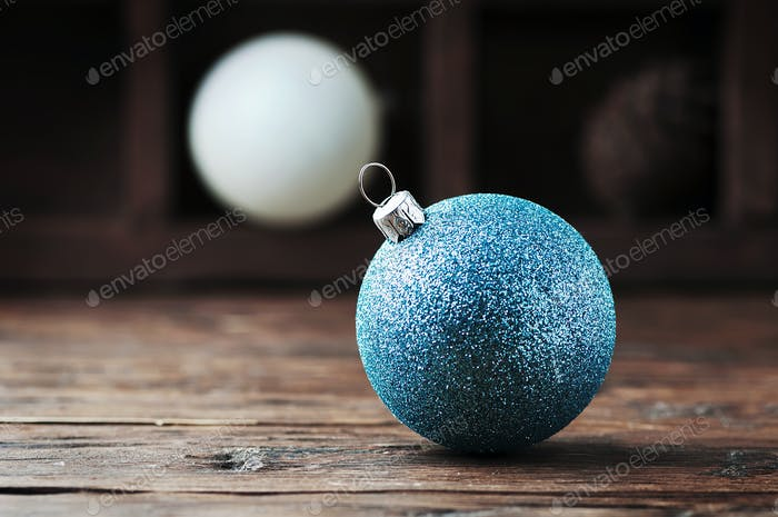 Weiße und blaue Weihnachtskugeln auf dem Holztisch