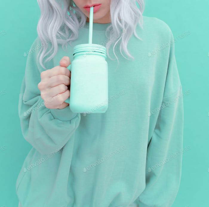Aesthetic girl in stylish mint clothing and fresh Smoothie. Pastel monochrome colours design