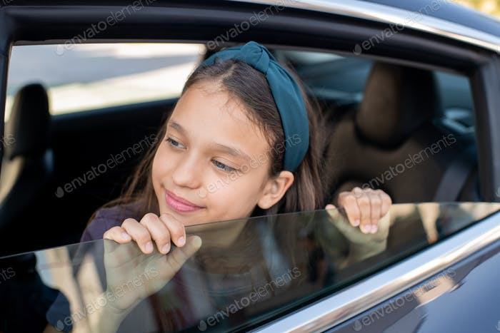 Adorable schoolgirl looking out of window of electric car