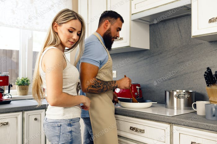 Young man and woman cooking food in kitchen together, happy couple preparing food