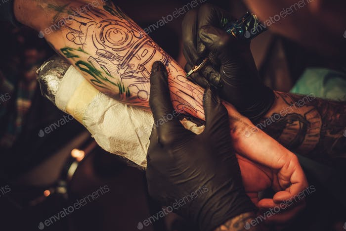 Tattoo artist makes a tattoo on a man's hand.