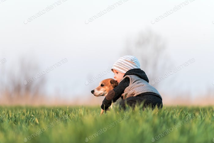 Small kid in yellow jacket with jack russel terrier puppy