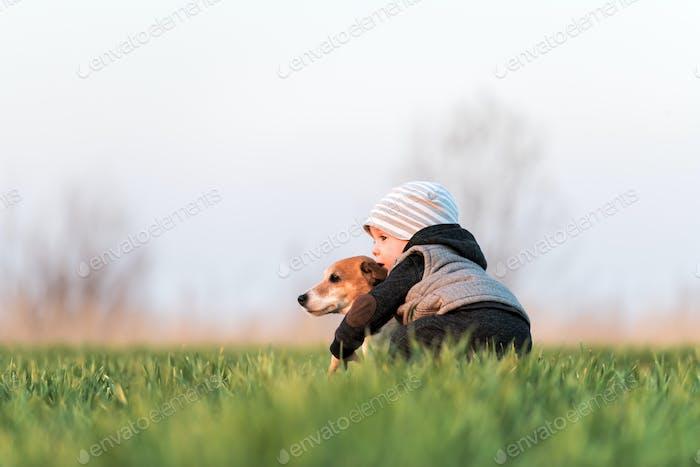 Kleines Kind in gelber Jacke mit Jack Russel Terrier Welpen