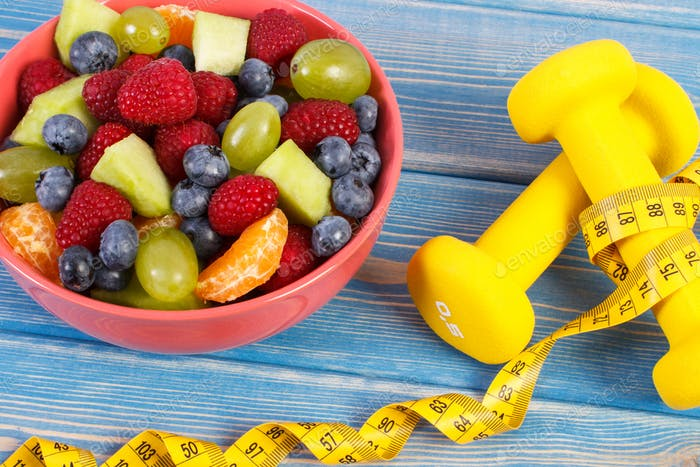 Fresh prepared fruit salad and centimeter with dumbbells, healthy lifestyle and nutrition concept