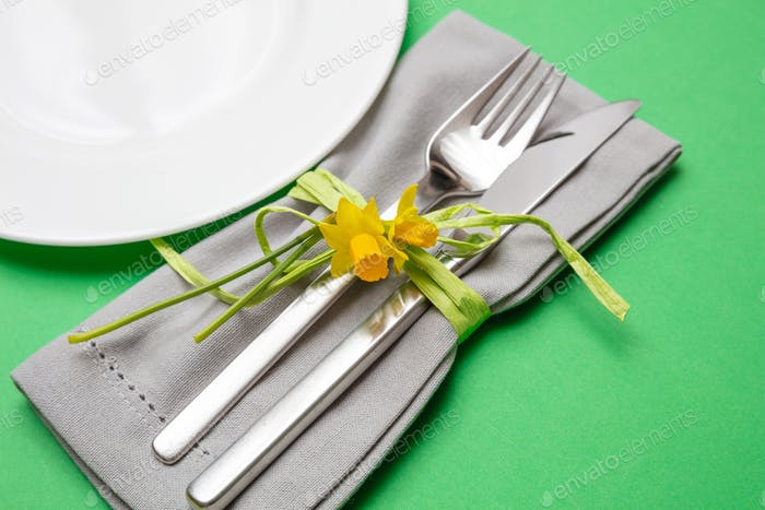 Table place setting in bright green. Gray linen napkin and white plate on green color background