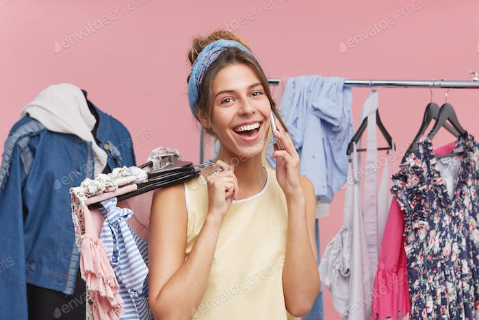 Happy beautiful woman having shopping day, choosing much clothes to buy, having conversation with so
