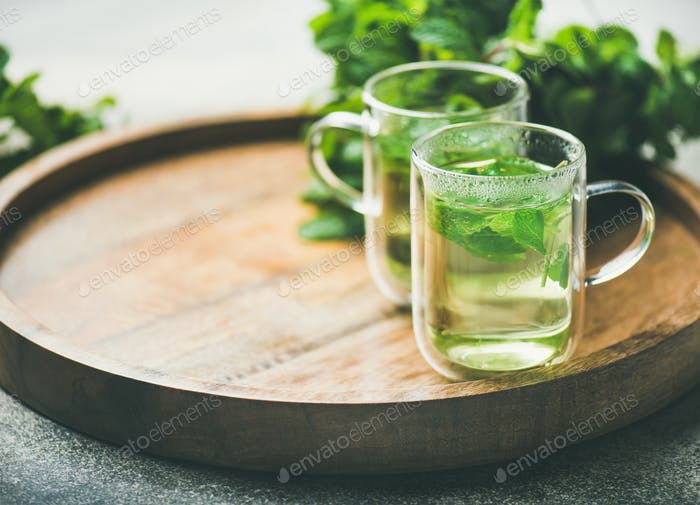 Hot herbal mint tea in glass mugs on tray