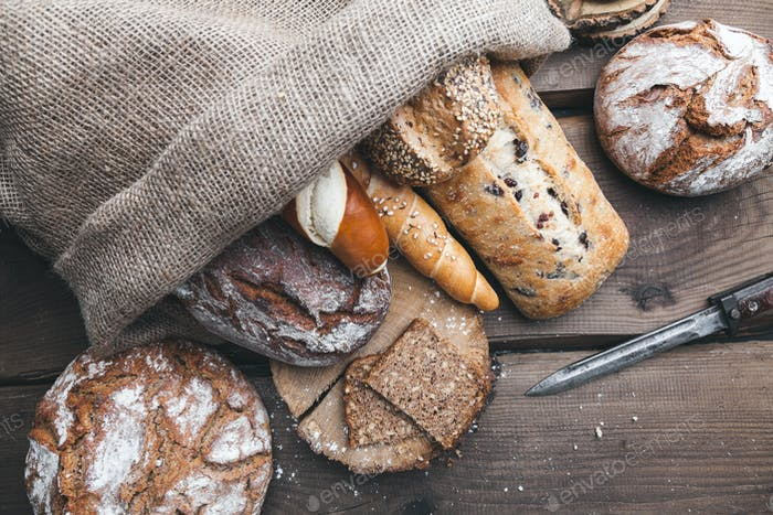 Delicious fresh bread inside a sack on wooden background